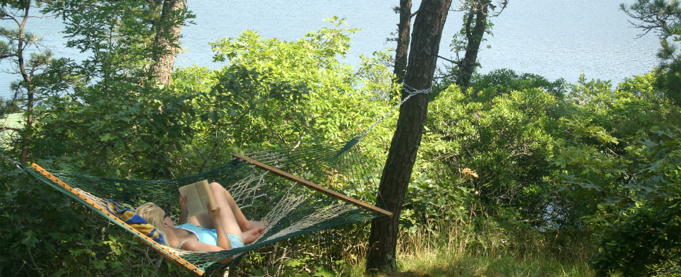girl reading book on hammock